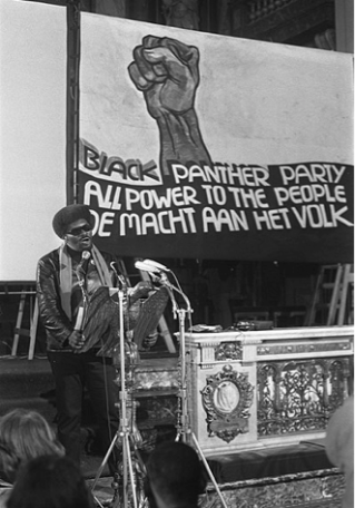 "A male Black Panther member addresses the crowd at a rally, speaking from a podium in front of a banner showing an upraised fist, and the slogan ""Black Panther Party: All power to the people/De macht aan het volk"". The speaker wears a dark leather jacket and a scarf, along with dark sunglasses."