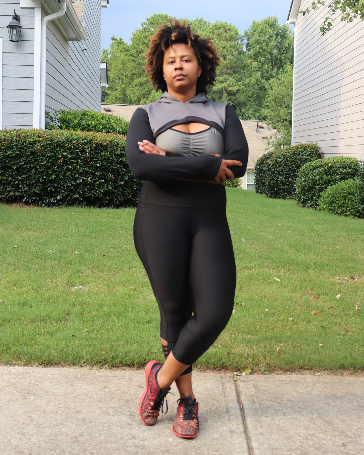 Tiffany stands on a sidewalk between two houses and yards. Her face is serious, as if she's about to show her workout that she means business. She's wearing her activewear: a stylish black and gray cropped warm-up hoodie, a gray sports bra with front ruching detail, and black high-waisted leggings with crossover elastic at the ankles. Her bright orange and gray sneakers stand out against the pavement of the sidewalk.