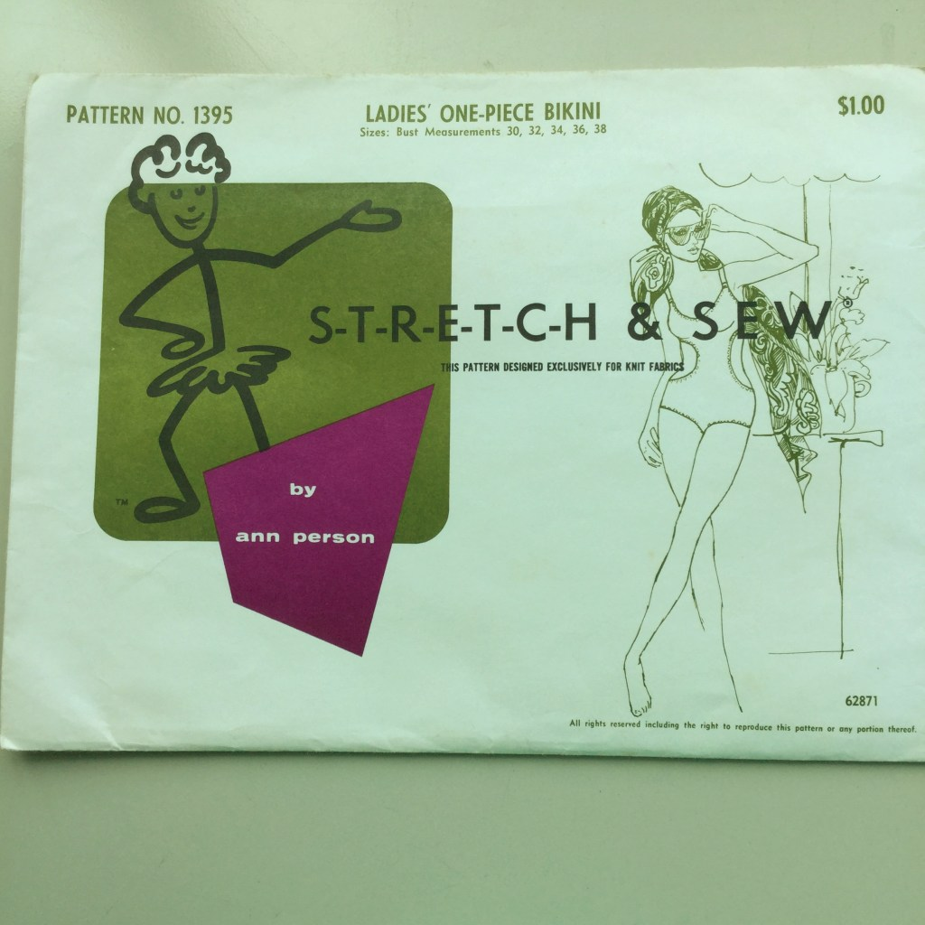 "Pattern envelope for Stretch and Sew pattern 1395, a ""Ladies' One-Piece Bikini"" from 1967. Envelope features a cartoon of the Stretch and Sew mascot and a line drawing of a woman leaning against a column in a monomaniacs."