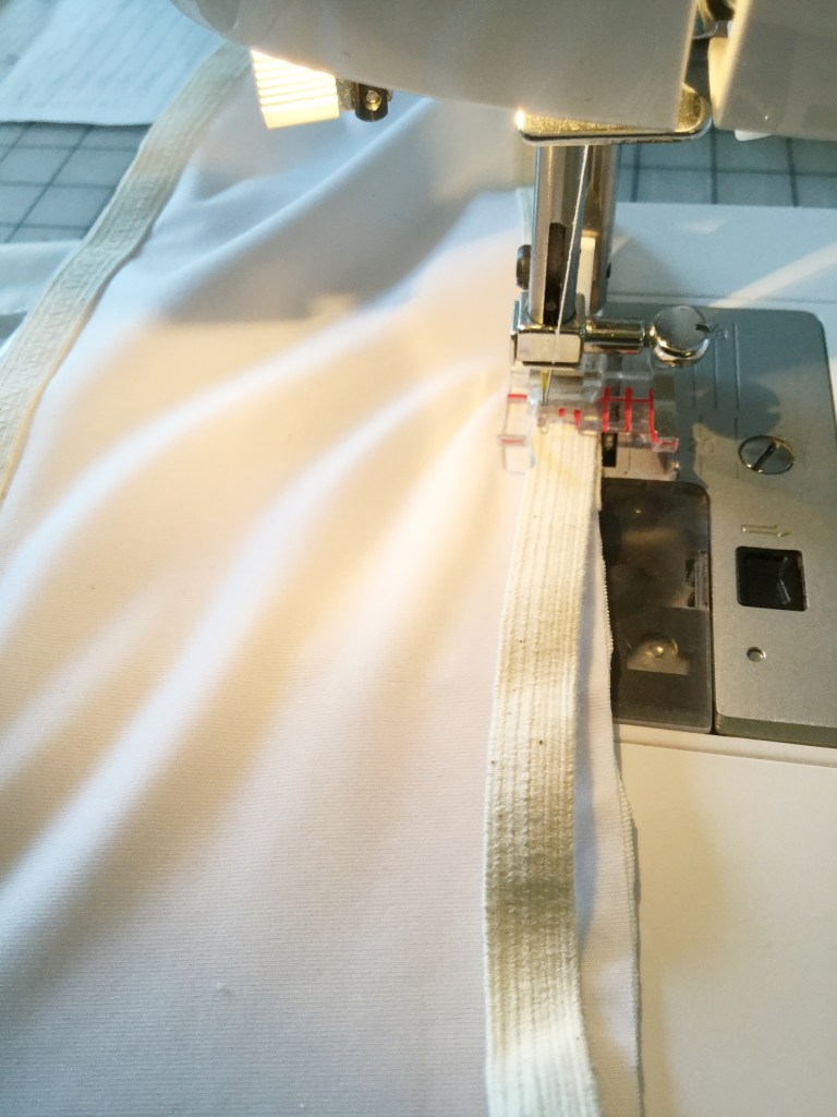 Photo showing elastic being sewn onto the edges of the swimsuit.
