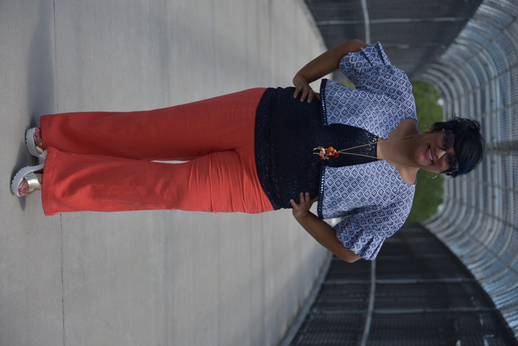Nandita in a her pattern mashup and pillowcase cropped jacket. She is standing on a bridge in salmon colored pants, navy sequined tank top, with blue and light blue diamond patterned crop jacket with pleated sleeves