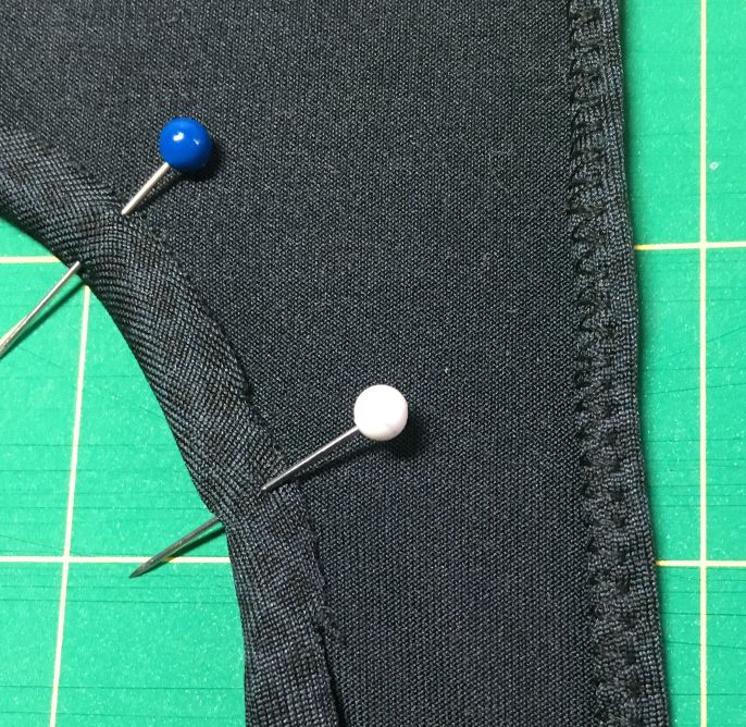 Image of two pins holding the folded neckline hem ready to be sewn.