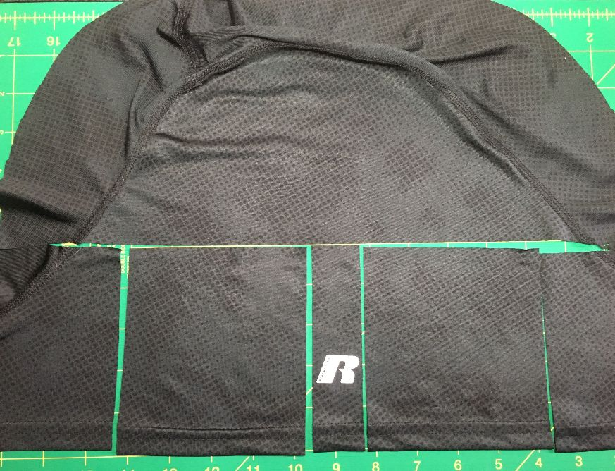 Image of the sleeve of a men's black T-shirt showing how to use the bottom of the sleeve to cut the pocket pieces for the slip.