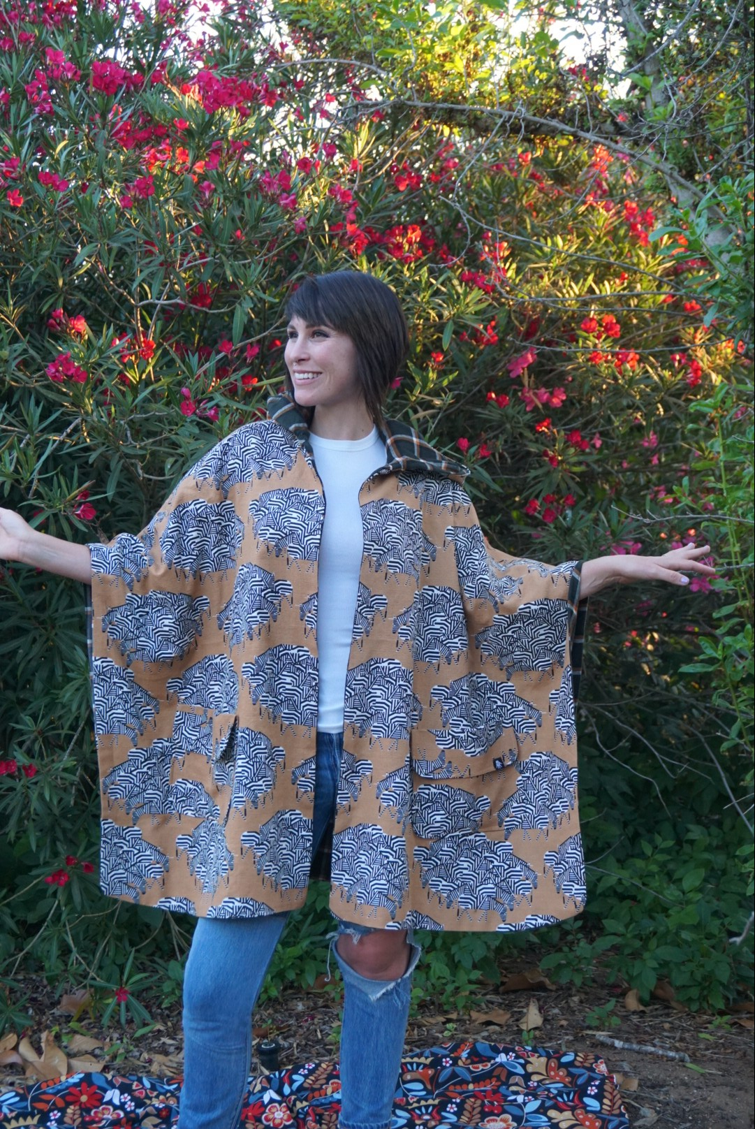 Mary stands in front of a wall of greenery and flowers. She extends her hands out to her sides to show the shape of her hooded poncho, which is goldenrod yellow with clusters of zebras placed throughout.