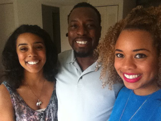 Picture of a father and his two daughters smiling at the camera.