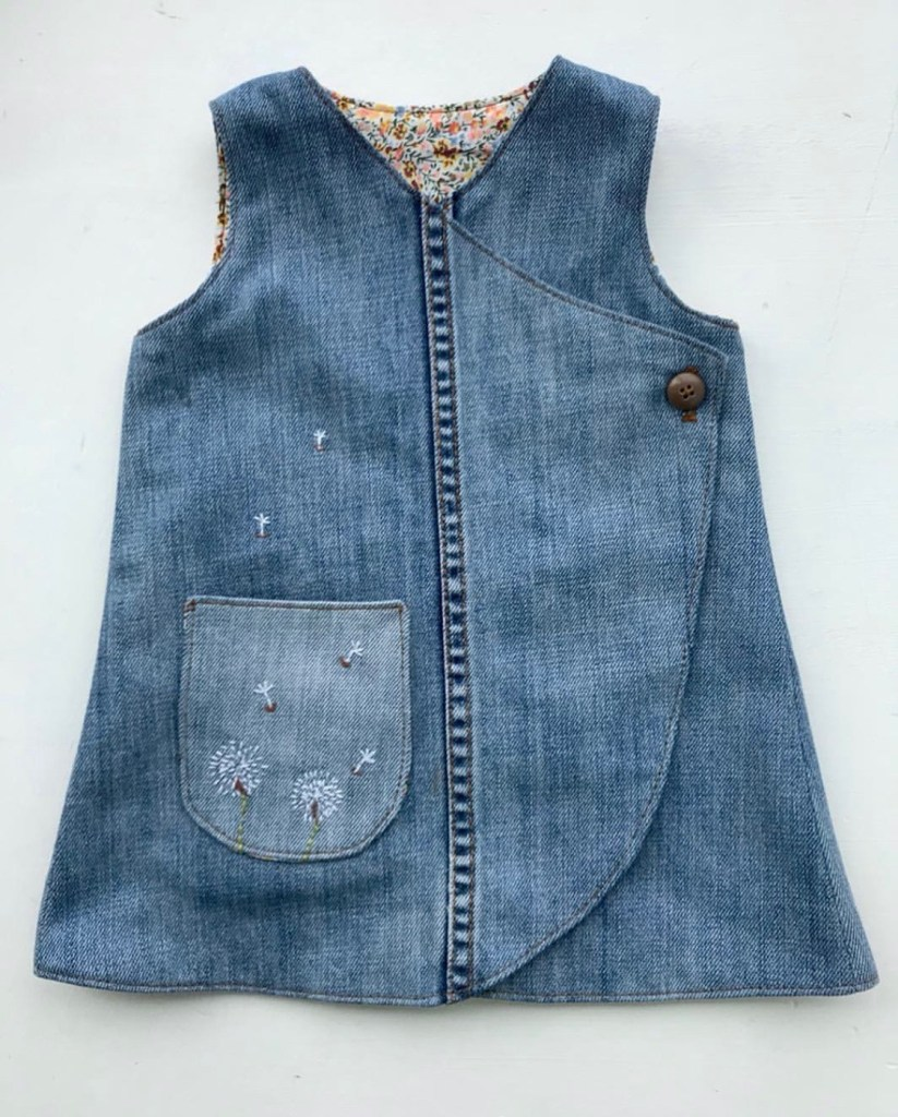 A flatlay of a child's pinafore dress, with an asymmetrical hem, a single button closure, and embroidered dandelion puffs on the pocket. The side seam of the jeans runs up the front of the dress.