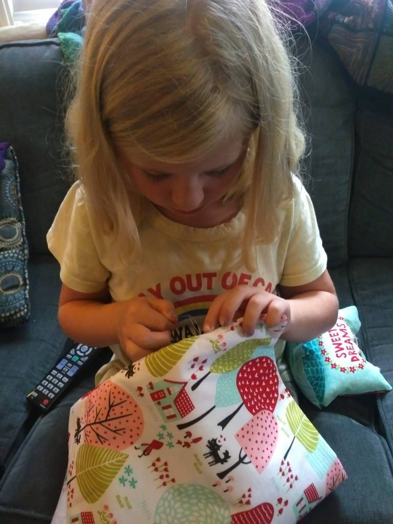 A child sits on the sofa, hand-stitching her lined doll blanket shut.