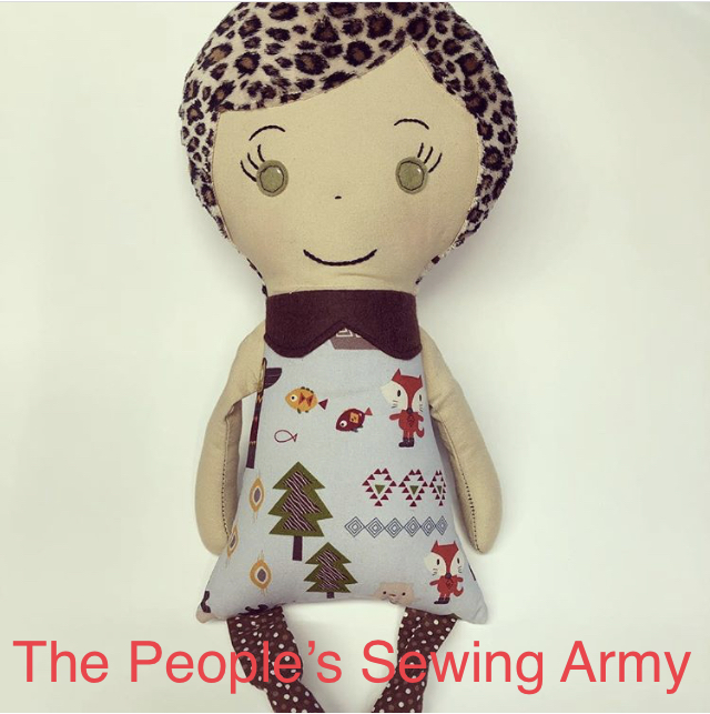 A doll, made from scrap fabric, sits against a white background. The doll was donated to The Community Transitional School.