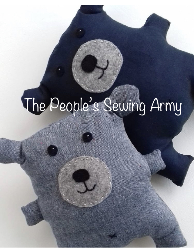Two stuffed teddy bears, one in light blue and the other in navy, are piled together on a white background. The bears were donated to The Community Transitional School.