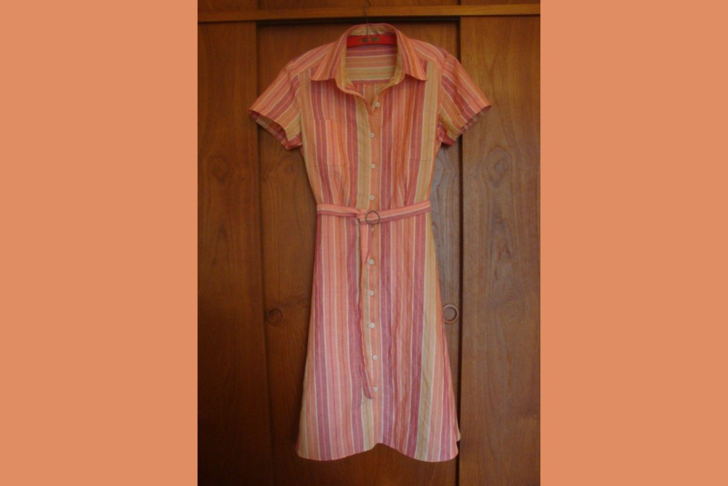 A shirtdress hangs on a wall. It has sherbet-coloured vertical stripes, white buttons, and a self belt.
