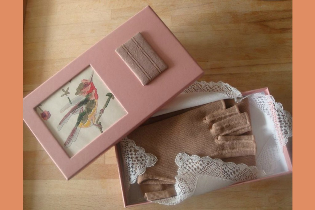 The author's therapeutic compression glove, presented in a decorative box with a vintage lace hankie, so that it feels like a luxury item rather than a medical one.