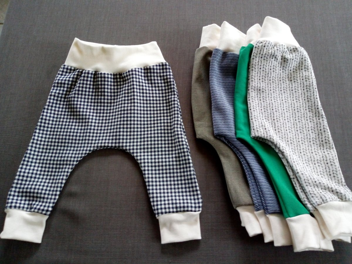 Pair of baby stretchy pants, with four more similar pairs folded in a pile next to it