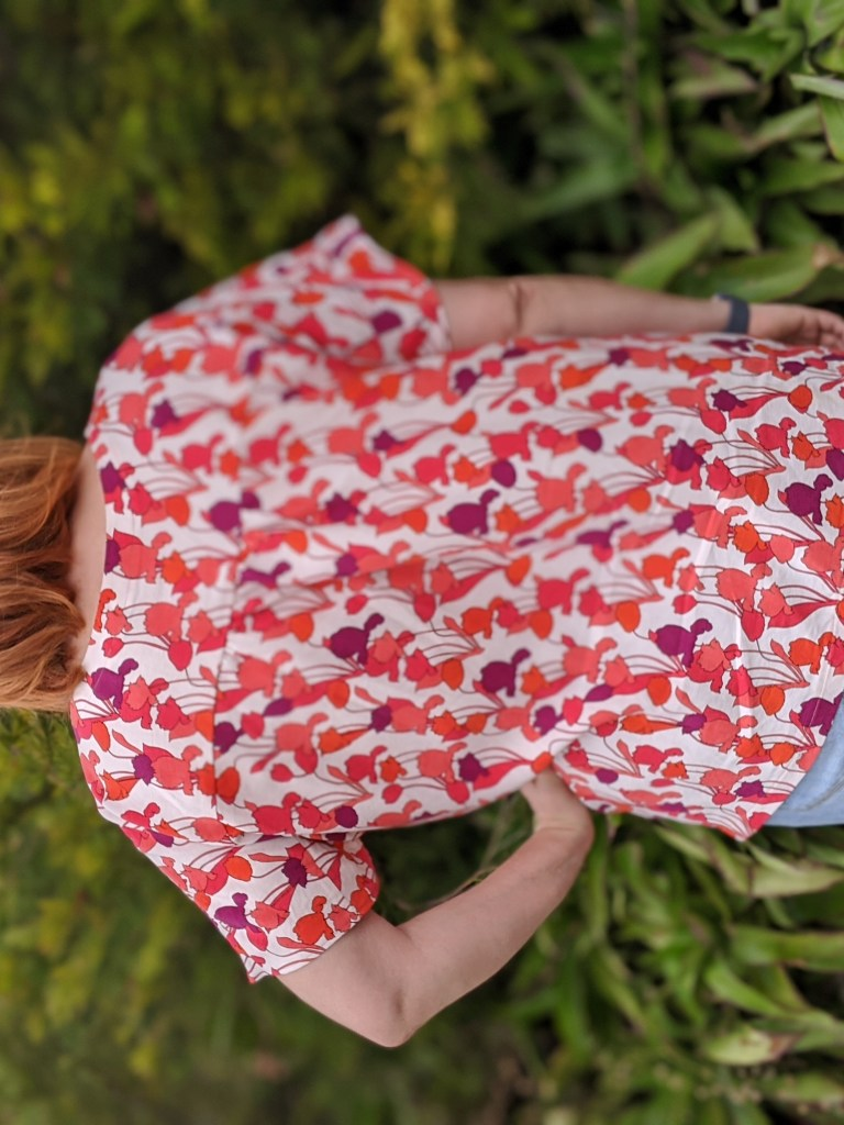 Back of a boxy top with large-scale red print on a white background, modeled on a redhead
