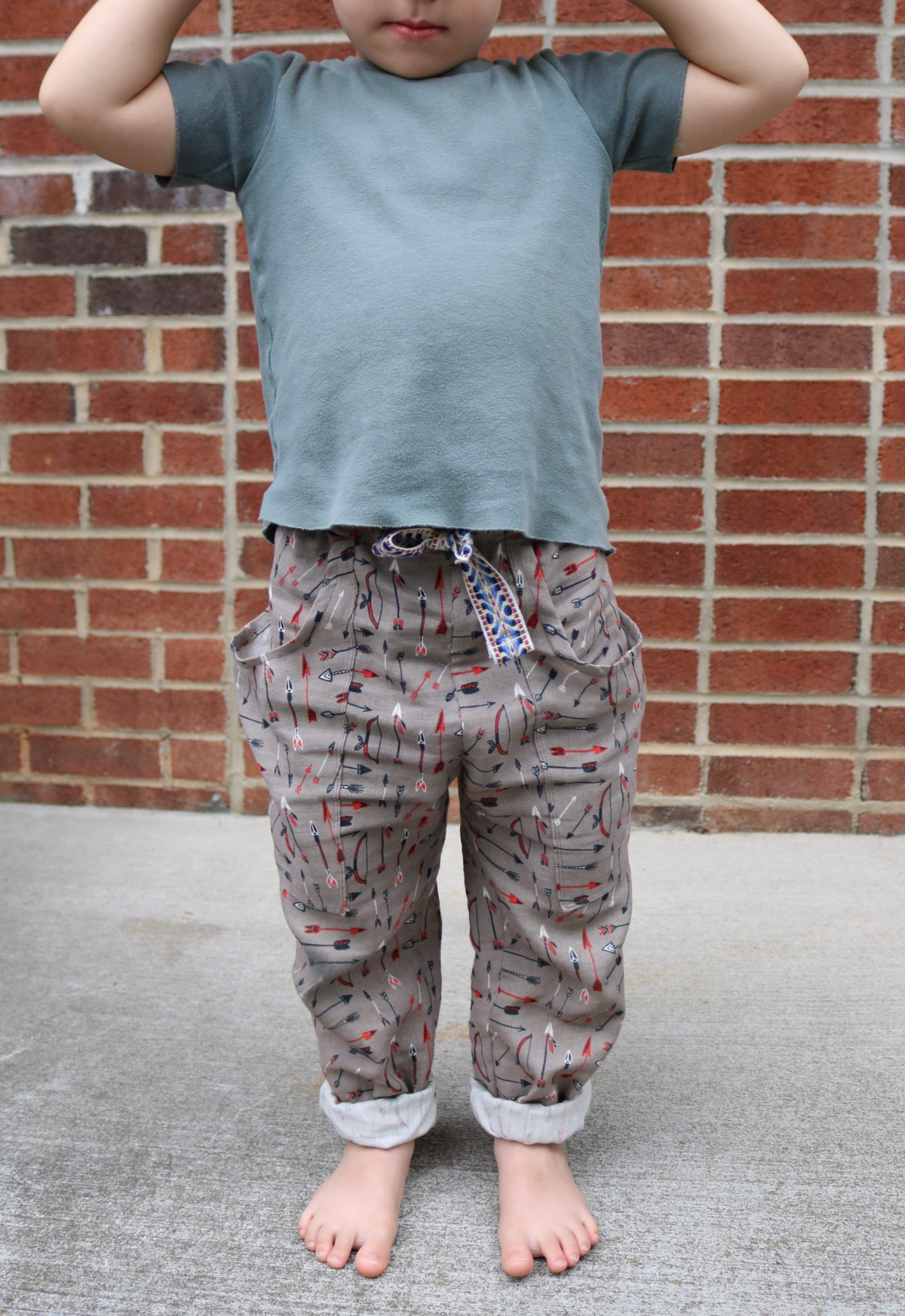 Preschool aged child in a blue shirt and pair of grey woven pants that have red, blue, and white arrows printed on them.