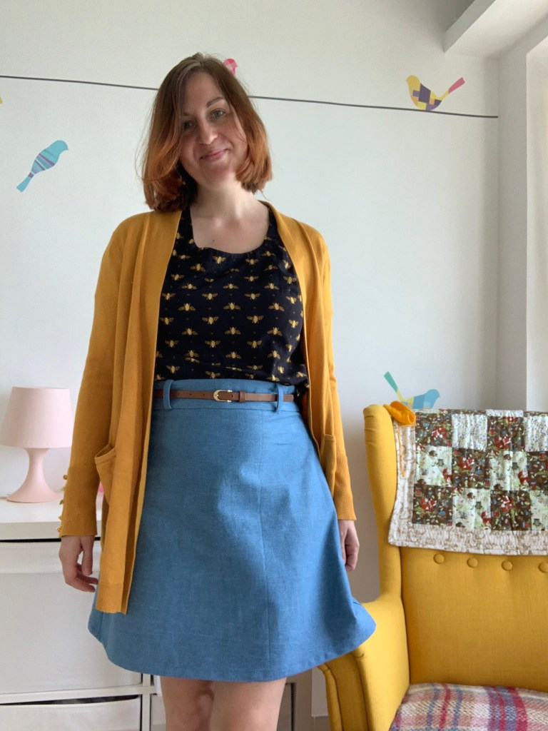 Sophy facing the camera and smiling.  She's wearing a dark top with a yellow design, a long gold cardigan and a belted jean skirt.