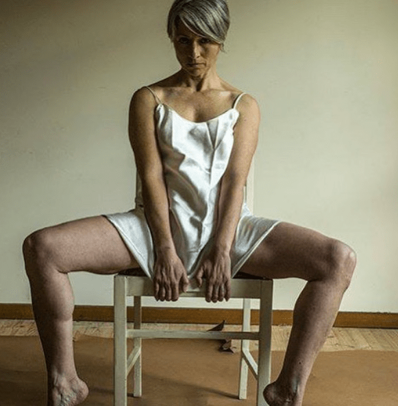Photo of 40+ year old woman in a silk chemise sitting opened legged but private parts covered on a chair, similar to a reverse cowgirl in a bistro chair stance.