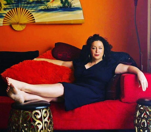 another glorious woman over 40 with long curly dark hair lounging back on a red couch in an orange room.