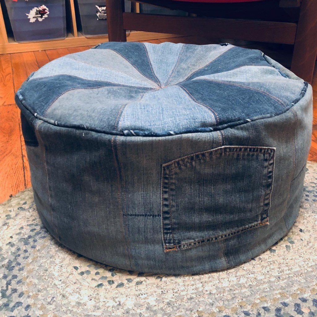 """Grace's Closet Case Patterns Pouf sits on a rug in her flat. The pouf is made from multiple pairs of recycled or thrifted jeans, with many colors and finishes visible. A back jeans pocket has been sewn to the """"face"""" of the pouf to serve as a handle for maneuvering the pouf."""