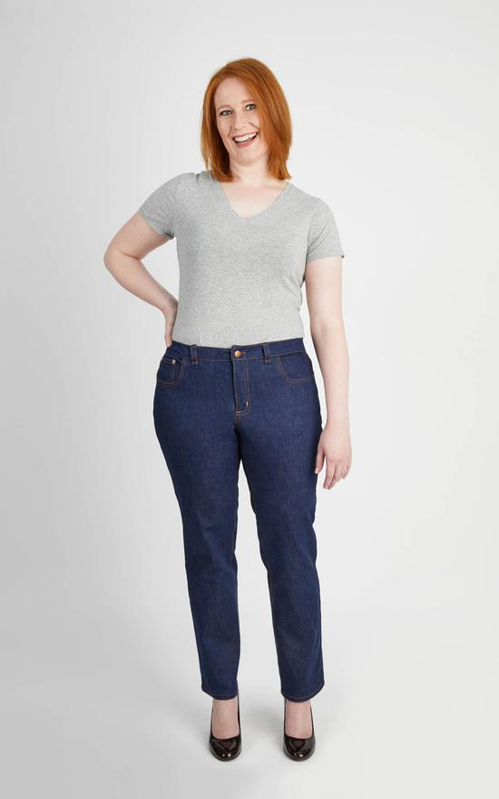 A red-haired woman models a pair of Cashmerette Ames jeans, which are paired with a gray v-neck tee and black patent court shoes. She is facing the camera, smiling, with her right hand on her hip.