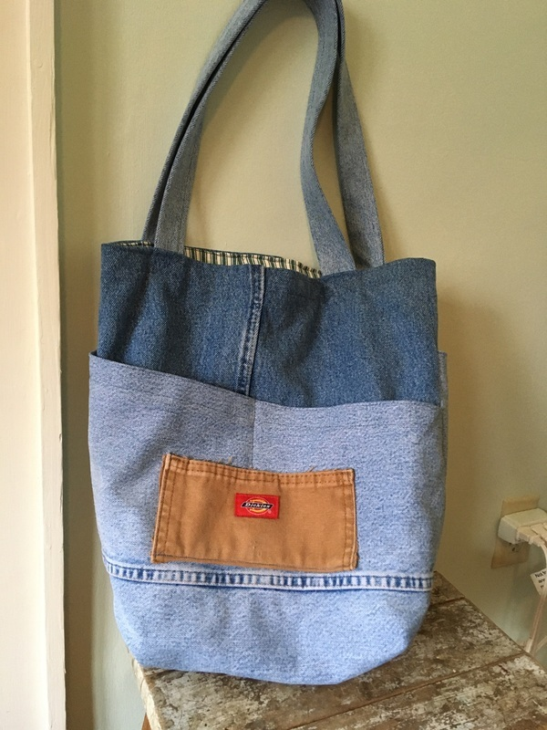 A Costa tote by Helen's Closet is shown, made of recycled/upcycled jeans and workwear. Three shades of denim are visible in the body and handles, and an exterior pocket has been made using a piece of a pair of Dickies workwear in their signature light brown color with their brand tag visible. The tote rests on a small table against a sage-colored wall.