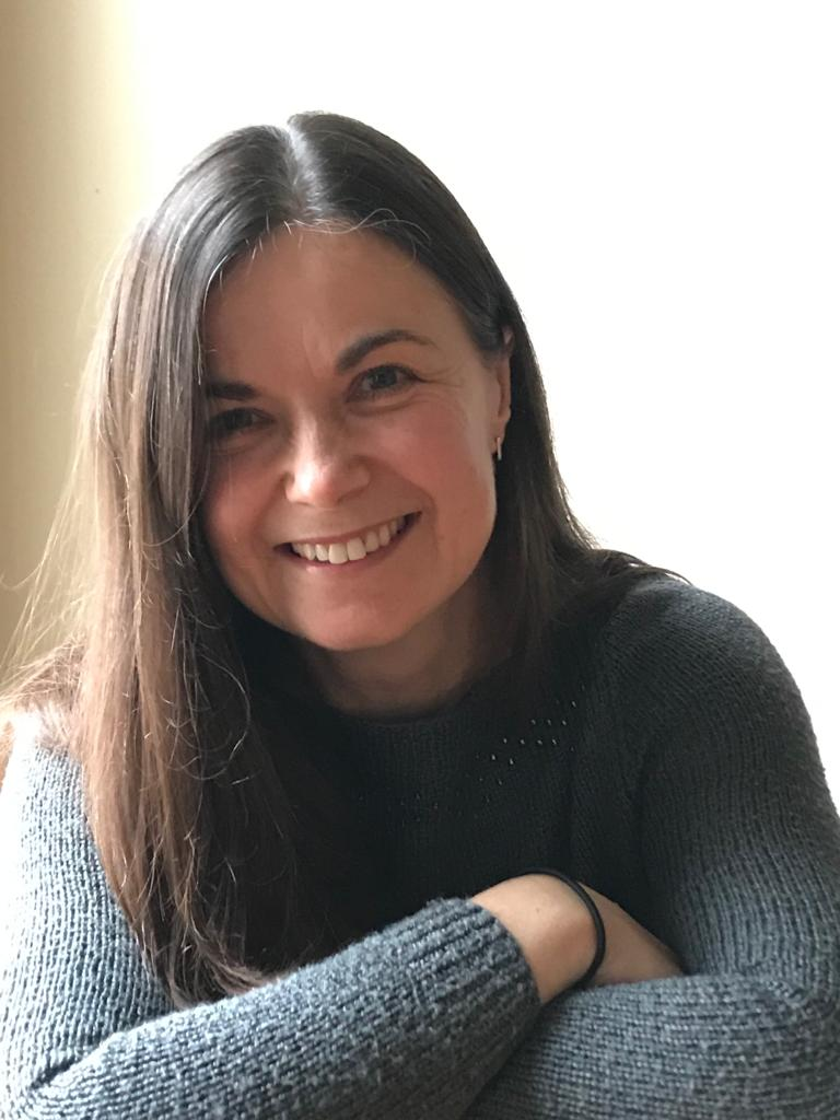 A picture of Jayne wearing a grey jumper looking at the camera and smiling.  Her arms are folded in front of her.