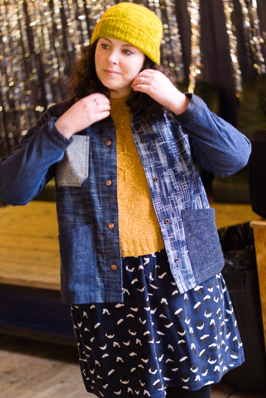 A white woman in a yellow knitted hat is fixing her hair wearing a yellow cardigan under an open denim jacket made from lots of different kinds of denim.