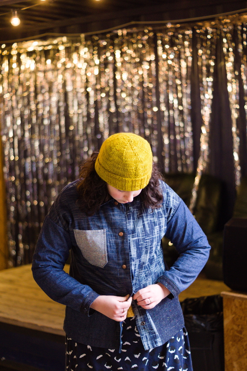 A white woman in a yellow knitted hat is looking down and buttoning up her denim jacket made from lots of different kinds of denim.