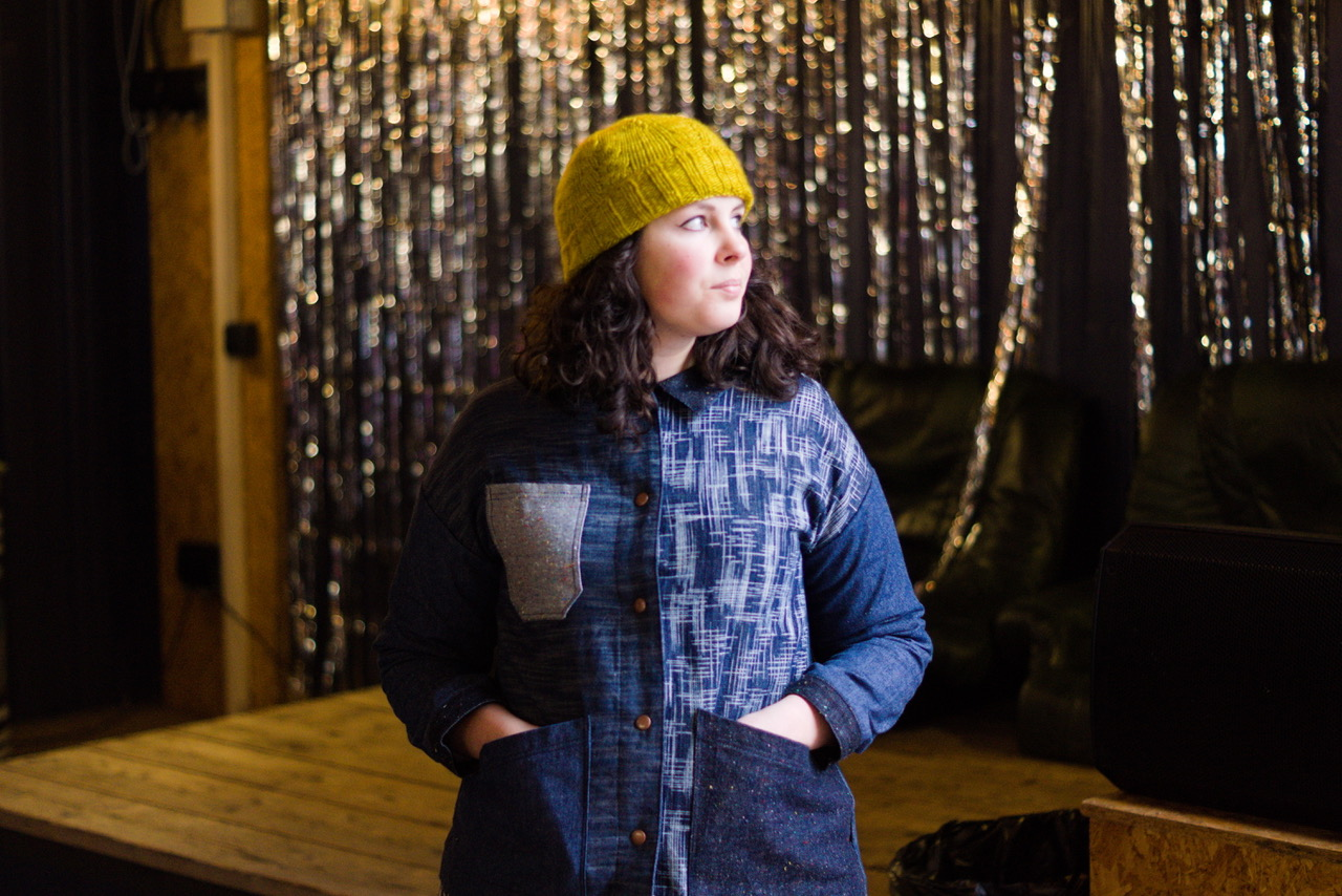 A white woman in a yellow knitted hat is looking up at the light with her hands in her pockets wearing a denim jacket made from lots of different kinds of denim.