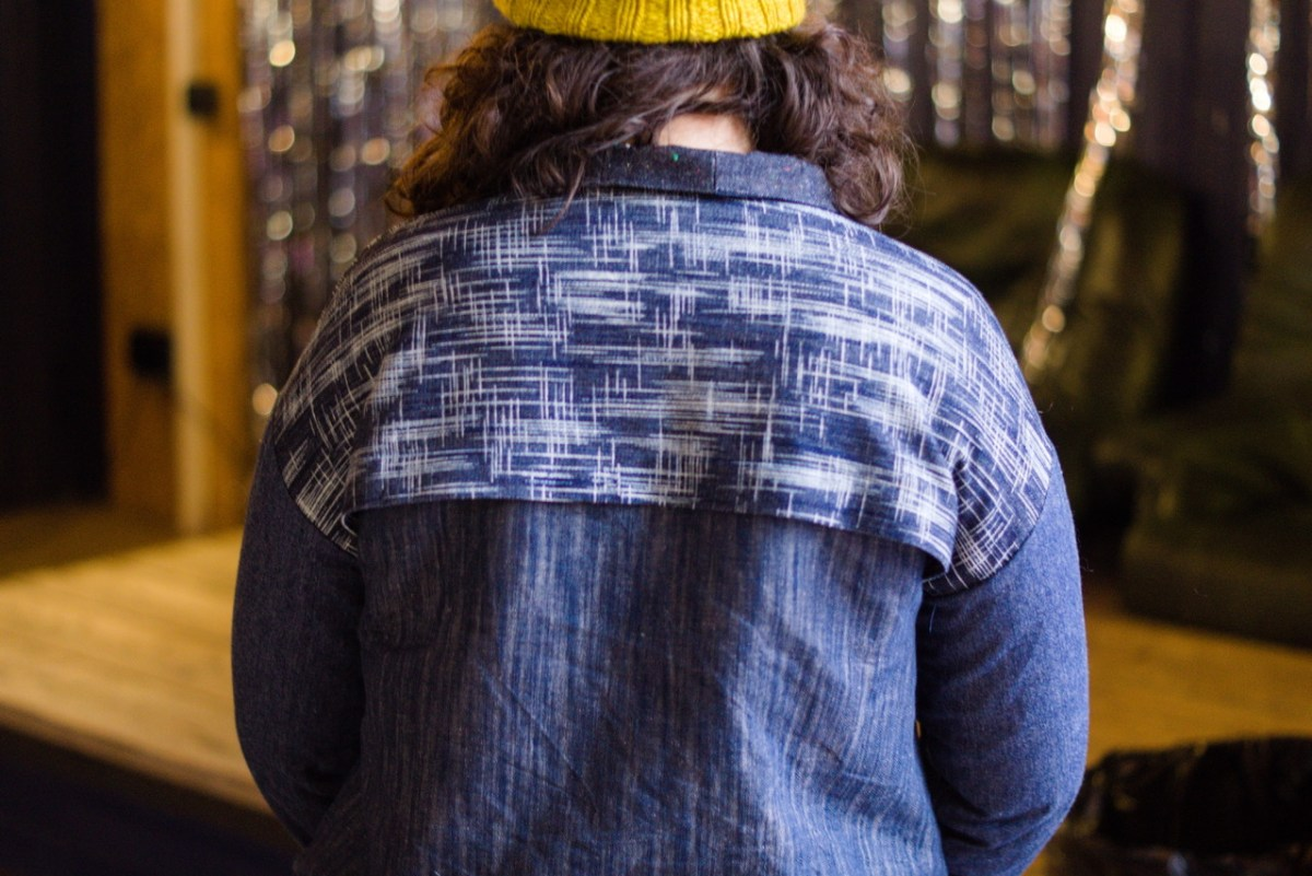 The photo shows the back of a woman with brown hair, the back of her denim jacket is made from several different shades of denim.