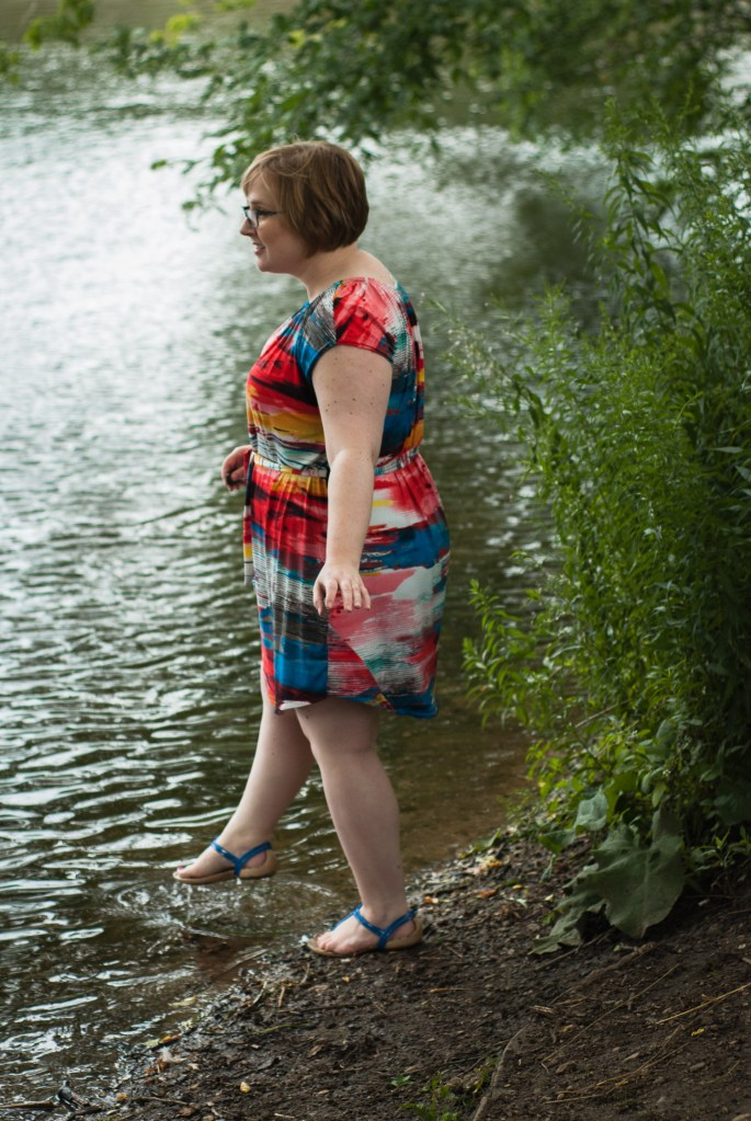 Blonde woman stands by a river, in a patterned dress that has a patched seam on the back hem.