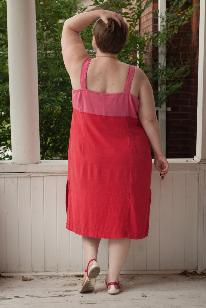 Woman stands looking away from camera in a pink and red linen dress with a secret seam off centre on the back of the dress.