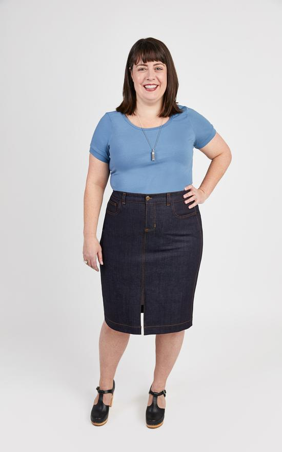 A young woman models a Cashmerette Ellis skirt made of denim. She is also wearing black clog heels and a sky blue knit tee with a scoop neck. A silver-colored pendant necklace hangs midway down her top. She holds her left hand on her hip and smiles while looking directly at the camera.