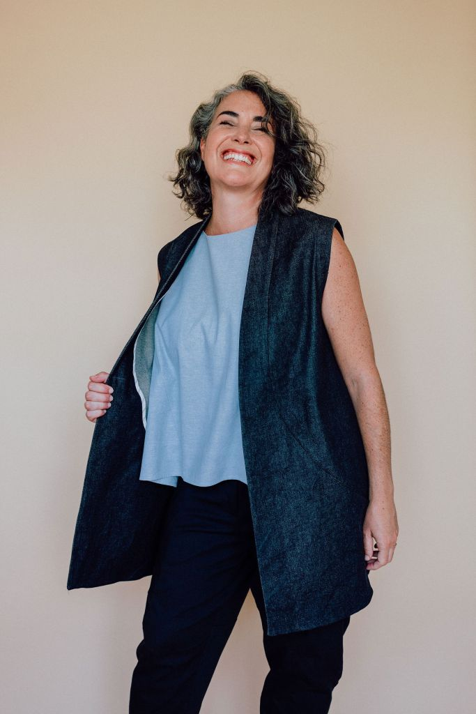 A woman models the In the Folds Flynn jacket as a sleeveless jacket. She is smiling broadly and her eyes are closed; her right hand pulls back the side of her jacket to reveal the wide facing and her sky blue boxy top. She is also wearing a pair of dark-colored trousers.