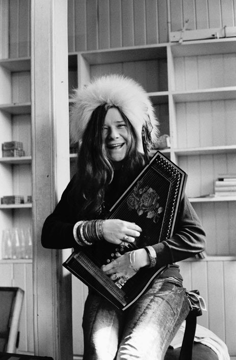 Image of singer Janis Joplin wearing a furry hat, a sweater, and a pair of denim jeans as she plays an autoharp