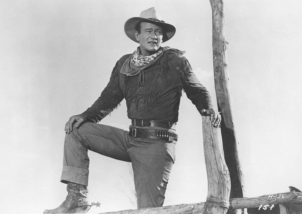 Image of John Wayne wearing a cowboy outfit with a cowboy hat, fringed shirt, bandolier belt, denim jeans, and cowboy boots with spurs.