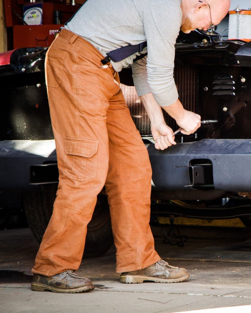 A man works on an older vehicle; he is wearing rust-colored work trousers, navy suspenders, a long-sleeved gray knit tee, and brown work boots.
