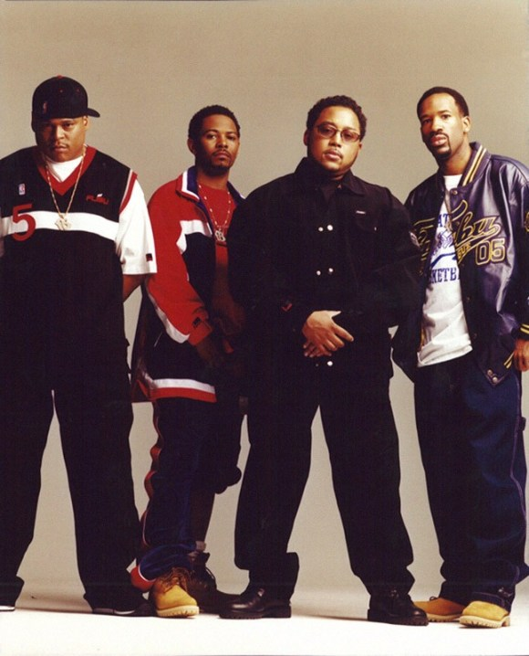 Image of four African-American me standing facing the camera, from left to right: the first one is wearing a snapback cap, a dark blue, white and red jersey, and dark jeans; the second one is wearing an oversized red, white and blue jacket and blue jeans; the third one is wearing black denim jacket and jeans; the last one is wearing a shiny FUBU purple jacket and blue jeans.