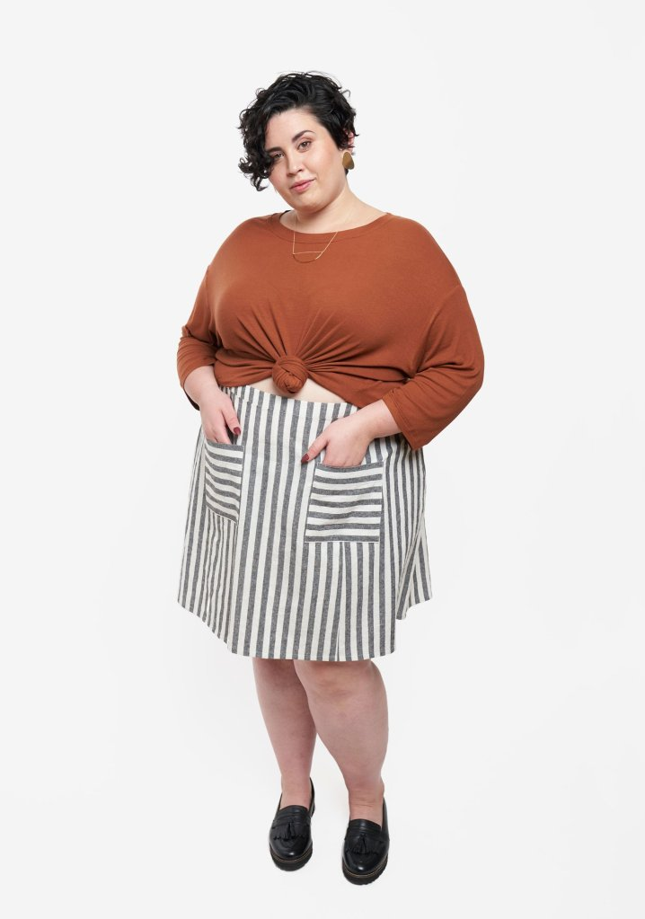 A model wears a Grainline Studio Reed skirt, which is made in a woven, striped fabric that is gray and white. The two front pockets of the skirt are cut on the cross-grain of the fabric, so that their stripes run parallel to the hem of the skirt; the body of the skirt features vertical stripes. The model also wears a rust-colored knit top knotted at her midriff. The model is curvy, and is modelling the newly-expanded size range of the new release from Grainline Studio.