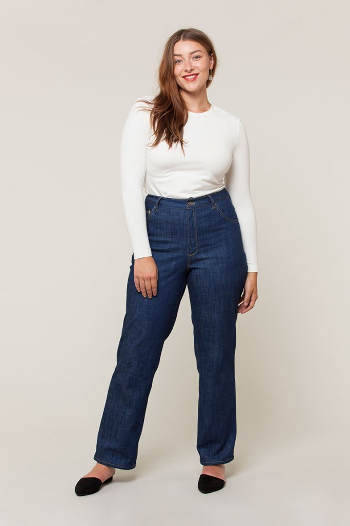 A model wears the Seamwork Tessa jeans, which are paired with black mule slides and a white knit long-sleeved tee. Her light brown hair falls over her right shoulder and she smiles at the camera.