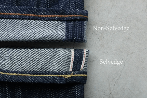 A close-up of two turned-back jeans hems, each from a different pair. The pair at the top of the photo is indigo dyed, and the turn-up shows overlocking at the seam allowances in matching dark blue thread. The pair at the bottom of the photo is also indigo dyed but is selvedge denim, as shown by the turn-up. The selvedge is white, with a single thread of red woven in.