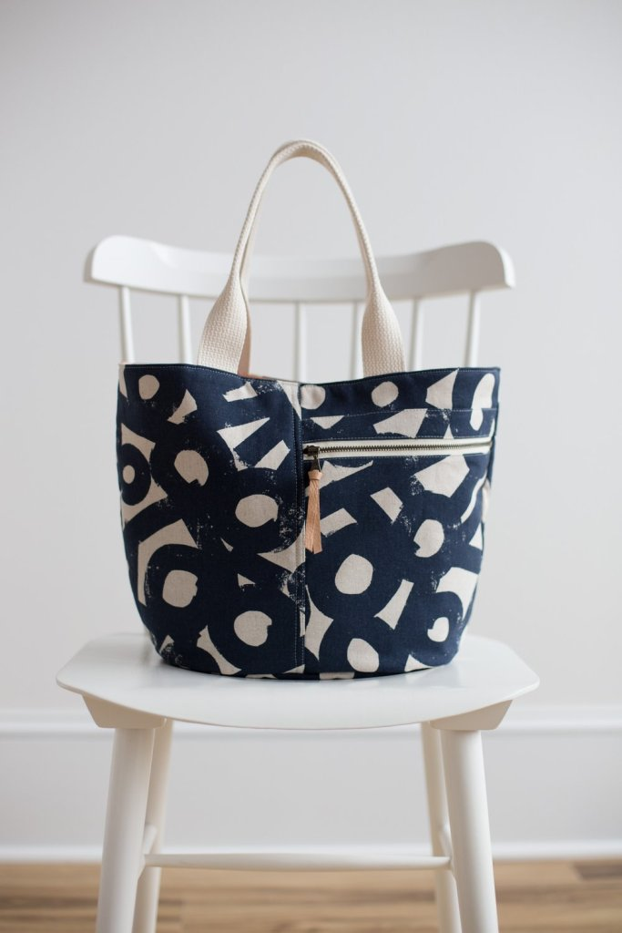A Noodlehead Crescent tote sits on a white armless chair in front of a white wall. The tote is made in a navy-and-white large-scale print and has ivory woven handles. The zipper tape is also ivory, and a tan leather pull has been added to the zipper.