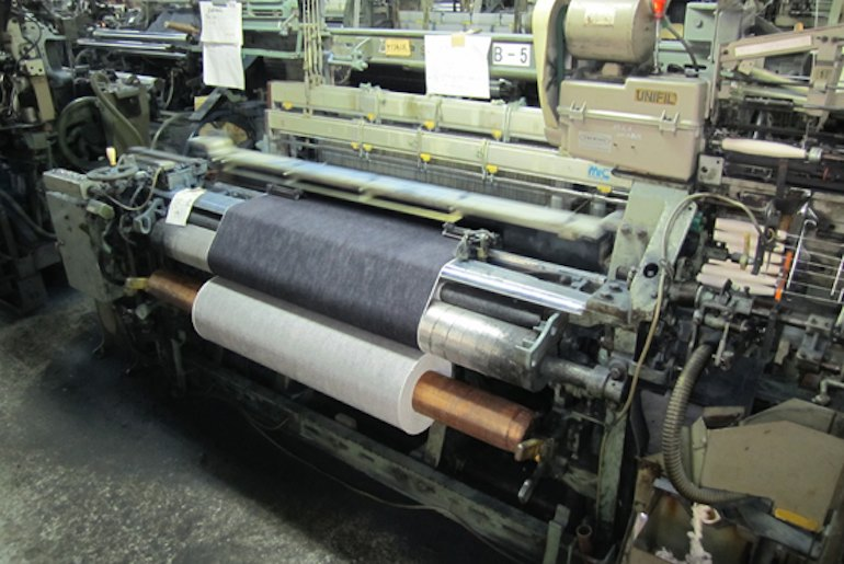 A shuttle loom in a textile factory, which is weaving a roll of indigo-dyed selvedge denim.