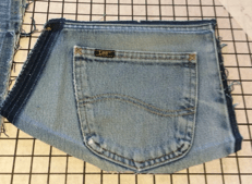 Unpicked left-side jeans pocket on a gridded board