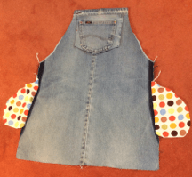 Front view of jeans pinafore showing sewn pocket bags in polka dot fabric and recycled pocket on the front