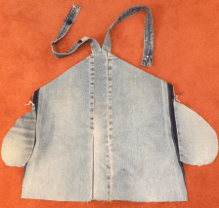 Back view of jeans pinafore showing denim pocket bag and recycled straps