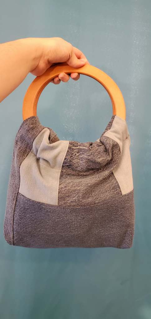 Front of a square, color-blocked denim bag with round wooden handles.
