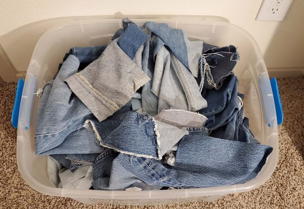 Plastic tub full of jeans cut into large pieces