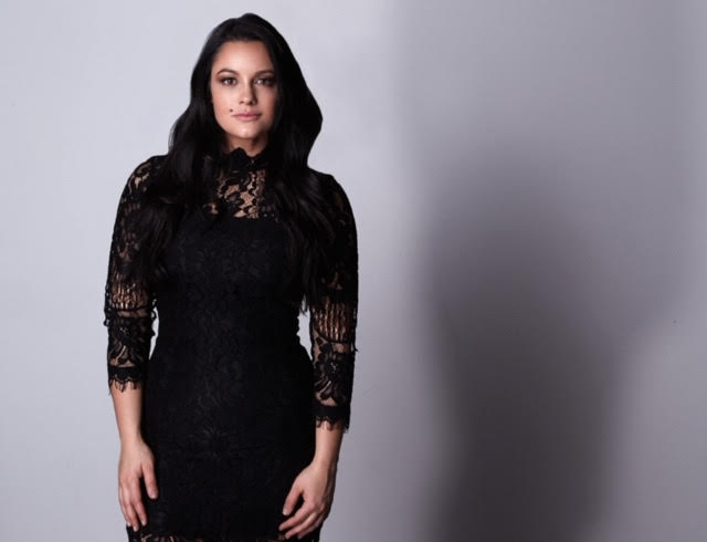 Jaclyn wears a black lace layer over a fitted black dress. She stands straight on to the camera, hands at her sides, and looks ahead confidently.