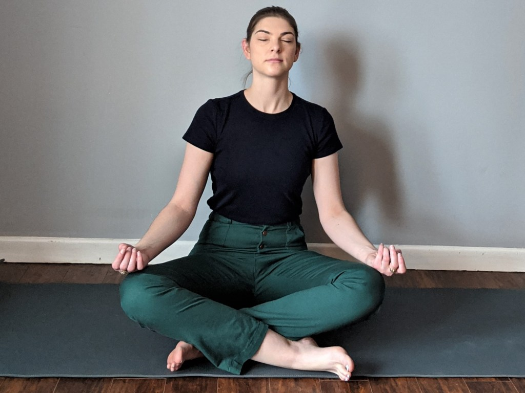 The author is sitting in a meditation pose wearing Lander pants
