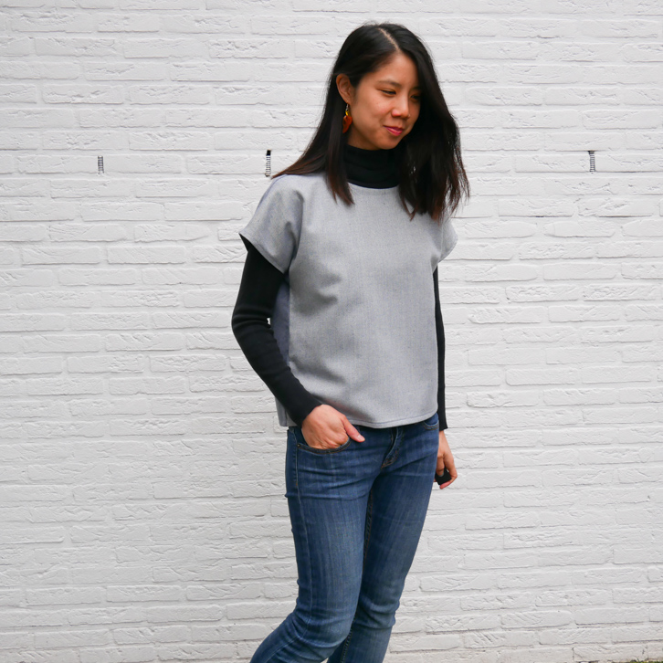 Front view of Kate in a loose denim top over a black turtleneck and jeans